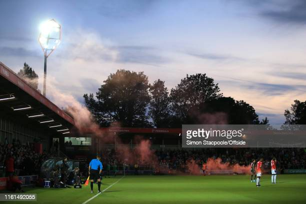 Smoke from a red flare drifts across the pitch at sunset during the Carabao Cup First Round match between Salford City and Leeds United at Moor Lane...
