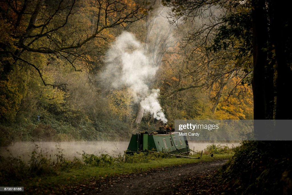 Smoke from a wood burner rises from a narrowboat moored on the Kennet and Avon canal near the Dundas Aqueduct as the sun rises on November 13, 2017 near Bath, England. After a warm autumn, with temperatures above average, much colder weather has arrived in many parts of the UK, signalling the start of more wintery weather for the coming few weeks.