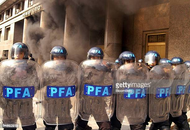 Smoke from burning tires fills the air as police block the entrance of the Finance Ministry where International Monetary Fund Director Rodrigo de...