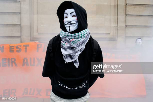 TOPSHOT Smoke from flares rises around a man wearing a Guy Fawkes mask during a demonstration in Paris on March 9 2016 called by various French...
