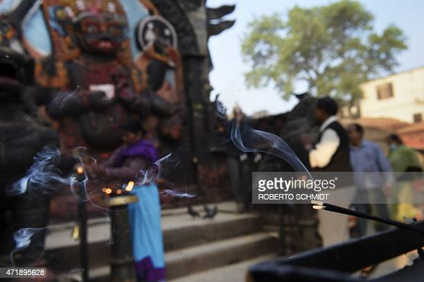 Smoke from incense sticks hangs in the air as Hindu devotees offer prayers in front of a statue of Hindu diety Kaal Bhairab in the Durbar Square...