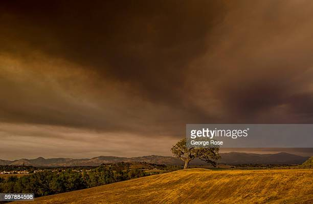 Smoke from the 33000acre Rey Fire billows into the air creating a spectacularly colorful sunset on August 20 in Solvang California Because of its...