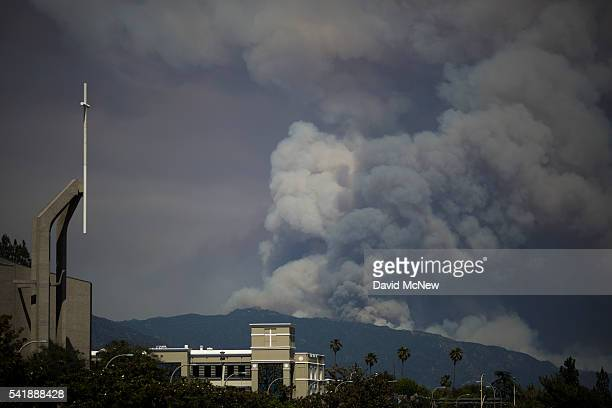 Smoke from the Fish Fire in the Angeles National Forest near Duarte California is seen beyond a church on June 20 2016 in Pasadena California The...