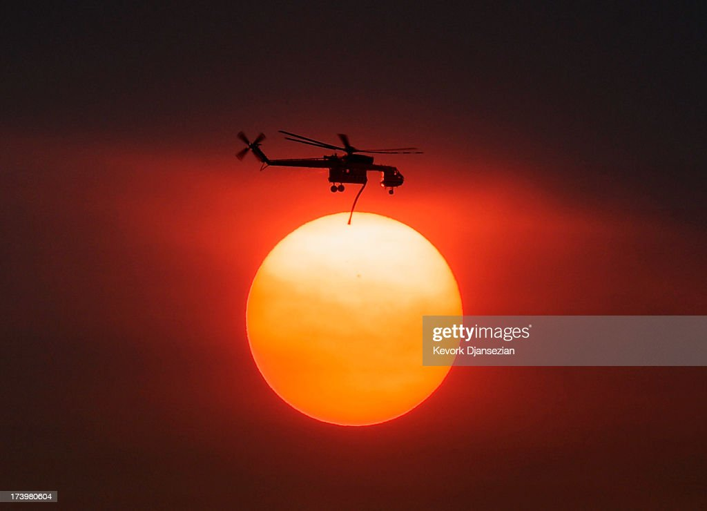 Smoke from the Mountain Fire obscures the sun as a fire fighting helicopter heads to fight the Mountain Fire after picking up water from Lake Hemet July 18, 2013 near Idyllwild, California. The massive wildfire in Riverside County has grown to 23,000 acres and is advancing towards the mountain town of Idyllwild on one front and city of Palm Springs on the other front destroying several homes and forcing the evacuation of 6,000 people.