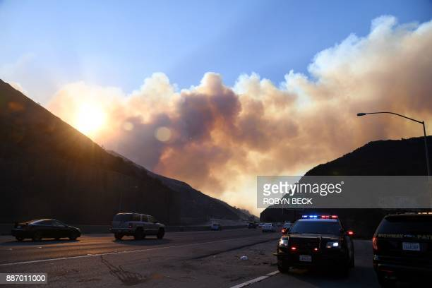 Smoke from the Skirball Fire rises above the 405 freeway near the Bel Aire area of Los Angeles California December 6 2017 / AFP PHOTO / Robyn Beck