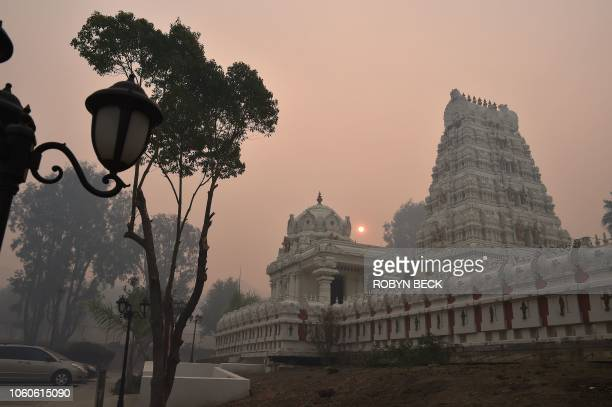 Smoke from the Woolsey Fire turns the sky red around the Malbu Hindu Temple November 10 2018 in Calabasas California The fire torn through the area...