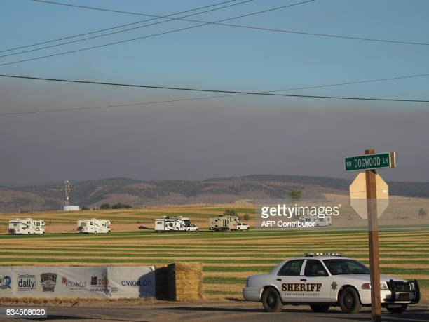 Smoke from wildfires darkens the sky as early visitors in campers and RVs arrive in Madras Oregon on August 17 to see the total solar eclipse on...