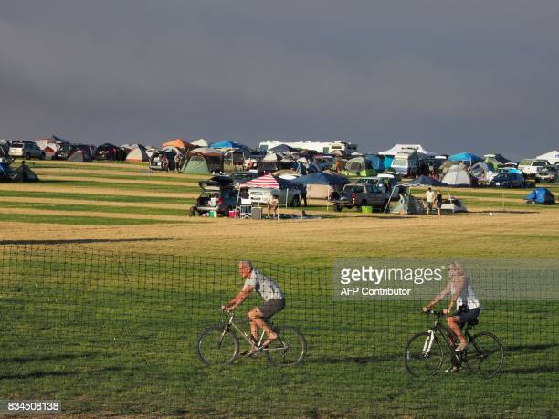 Smoke from wildfires darkens the sky as early visitors take a bike ride in 'SolarTown' in Madras Oregon on August 17 to see the total solar eclipse...