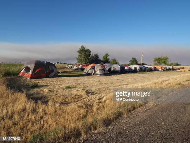 Smoke from wildfires darkens the sky as tents on a farmer's field await the arrival of visitors in Madras Oregon on August 17 to see the total solar...