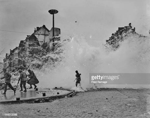 Smoke grenade explodes as soldiers of the 3rd Armored Division, First Army Corps of the United States advance through the ruins of Cologne on 7th...