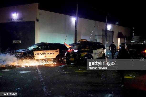 Smoke grenade ignites beneath a vandalized police cruiser at the Portland Police Bureau North Precinct during a protest against police brutality and...