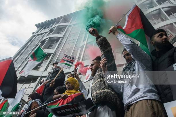 Smoke grenades are let off as tens of thousands of people join a protest march in solidarity with Palestine to the Israeli Embassy on May 15, 2021 in...