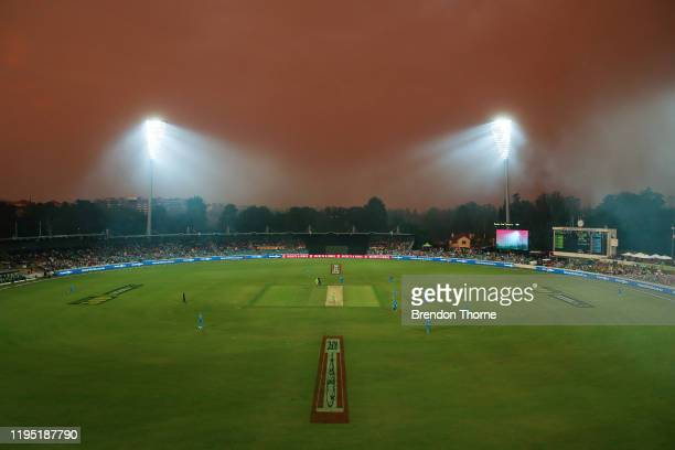 Smoke haze from bushfires forces a stoppage to play during the Big Bash League match between the Sydney Thunder and the Adelaide Strikers at Manuka...
