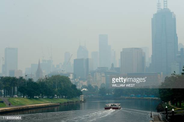 Smoke haze from unprecendented bushfires hover over the city skyline ahead of the Australian Open in Melbourne on January 14 2020 Soaring pollution...