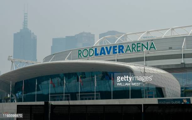 Smoke haze from unprecendented bushfires hover over the Rod Laver Arena ahead of the Australian Open in Melbourne on January 14, 2020. - Soaring...