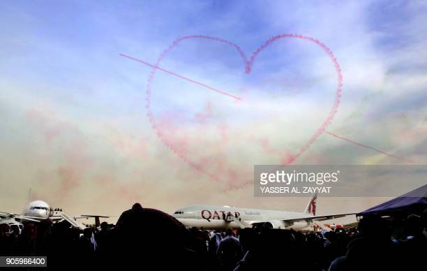 TOPSHOT Smoke in the shape of a heart is seen in the sky above a Qatar Airways plane during the Kuwait aviation show in Kuwait City on January 17...