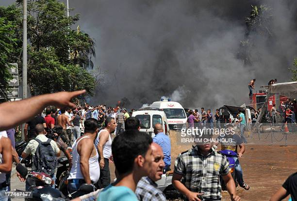 Smoke is seen above rescuers and people gathering on the site of a powerful explosion in the northern Lebanese city of Tripoli on August 23 2013 Two...