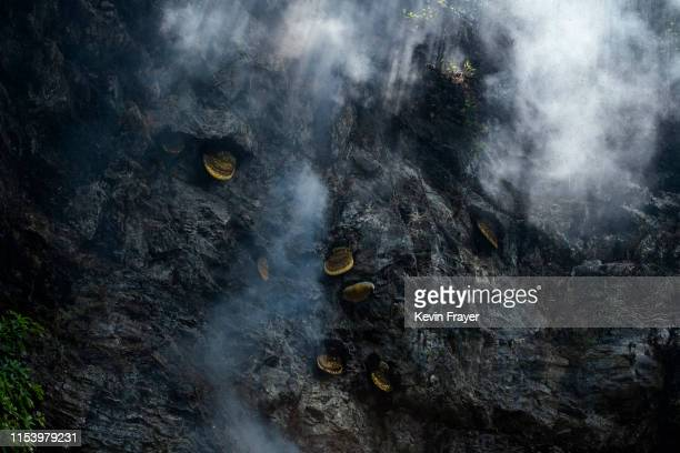 Smoke is seen around hives where Chinese ethnic Lisu honey hunters were gathering wild cliff honey in a gorge on May 10 2019 near Mangshi in Dehong...