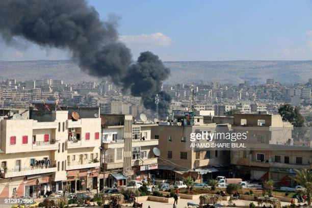 TOPSHOT Smoke is seen billowing from the northern Syrian Kurdish town of Afrin on January 31 2018 Turkey and allied Syrian rebel groups launched...