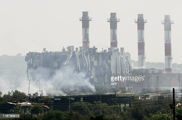 Smoke is seen in front of a damaged building by the power station in Mari on July 11 2011 after huge explosions reportedly from seized munitions...