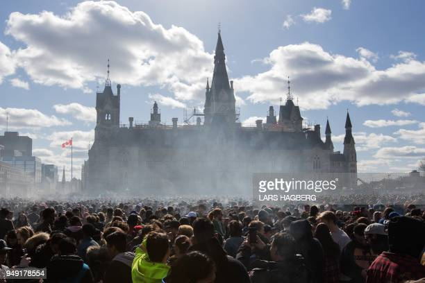 Smoke lingers over Parliament Hill as people smoke marijuana during the annual 4/20 rally on Parliament Hill in Ottawa Ontario on April 20 2018
