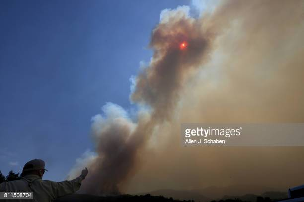 Smoke obscures the sun as a US Forest Service official watches the Whittier Fire burn towards SR154 in the Los Padres National Forest near Lake...