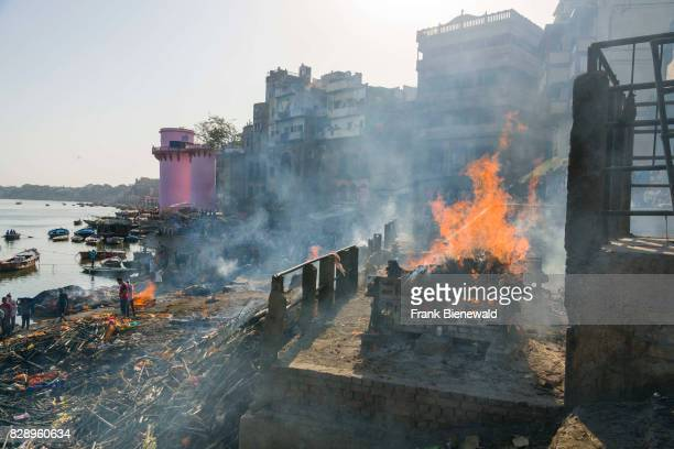 Smoke of cremated dead bodies is rising at Manikarnika Ghat at the holy river Ganges in the suburb Godowlia.