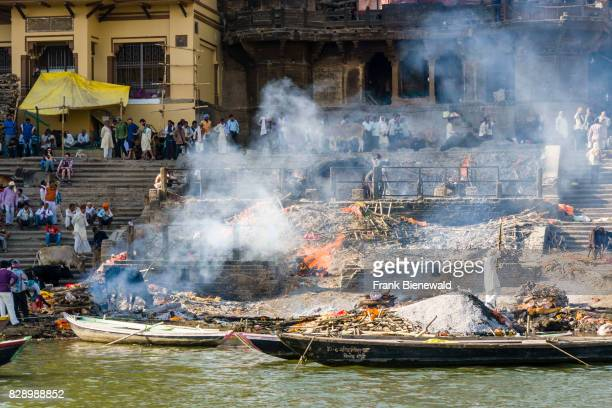 Smoke of cremated dead bodies is rising at Manikarnika Ghat at the holy river Ganges in the suburb Godowlia