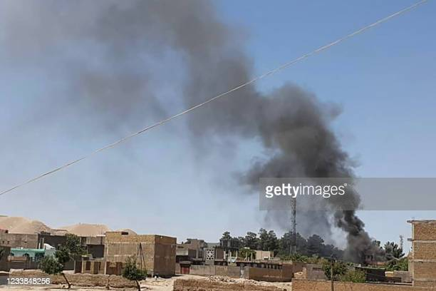 Smoke plume rises from houses amid ongoing fight between Afghan security forces and Taliban fighters in the western city of Qala-i- Naw, the capital...