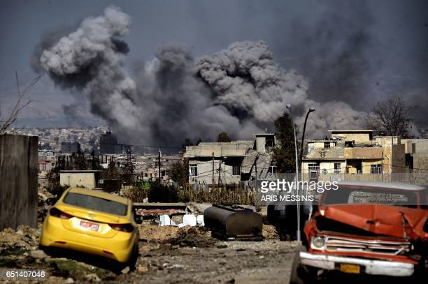 TOPSHOT Smoke plumes rise after an airstrike in west Mosul on March 10 2017 as Iraqi forces advance in the city during the ongoing battle to seize it...