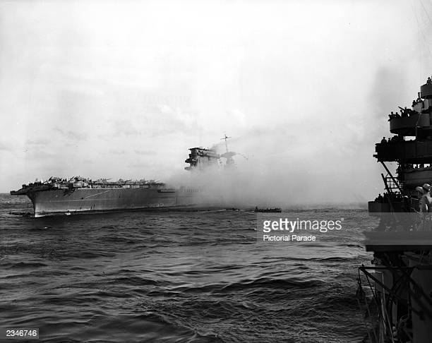 Smoke pours from the aircraft carrier the USS Lexington from Japanese torpedo hits during the Battle of the Coral Sea in World War II, 1942.