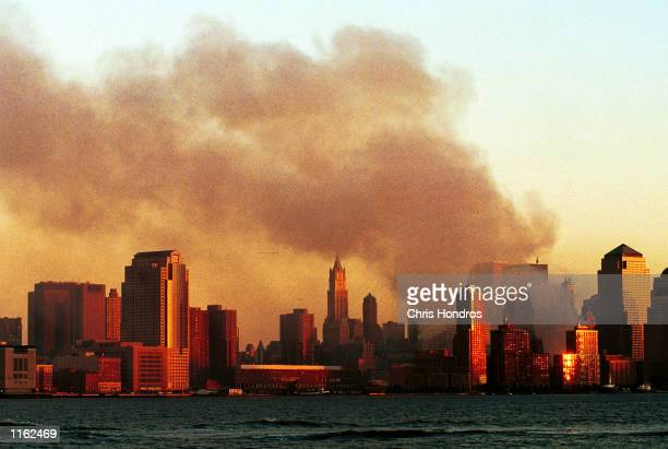 Smoke pours from the former site of the World Trade Center in Manhattan September 12, 2001 from a vantage point in Hoboken, N.J. Smoke filled the air...