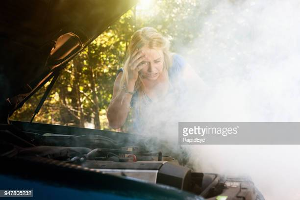 smoke pours from young woman's car engine - broken down car stock pictures, royalty-free photos & images