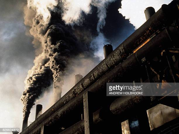 Smoke pours out of a factory in Copsa Mica, Romania. The billowing, carcinogenic black clouds of carbon black, used for dyes and tires, pollutes and...