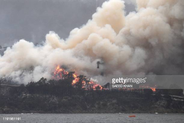 Smoke raises to the sky as a woodchip mill burns in Eden, in Australia's New South Wales state on January 6, 2020. - January 5 brought milder...