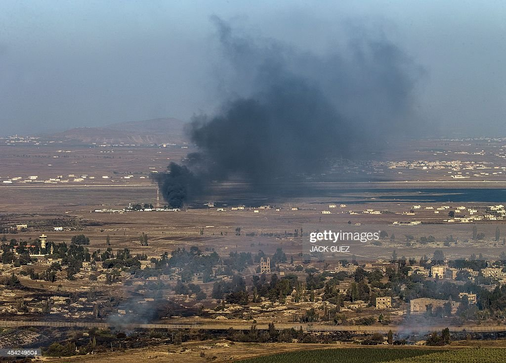 Smoke rise from the Syrian village of Quneitra, as seen from the Israeli-occupied Golan Heights, as a result of fighting between forces loyal to Syrian President Bashar Assad and rebels over the control of the Quneitra border crossing, the only official crossing between Syria and the on August 27, 2014. Syrian rebels, including Al-Qaeda's affiliate Al-Nusra Front, seized control of the Syrian crossing with the Israeli-occupied Golan Heights today, the Britain-based Syrian Observatory for Human Rights said.