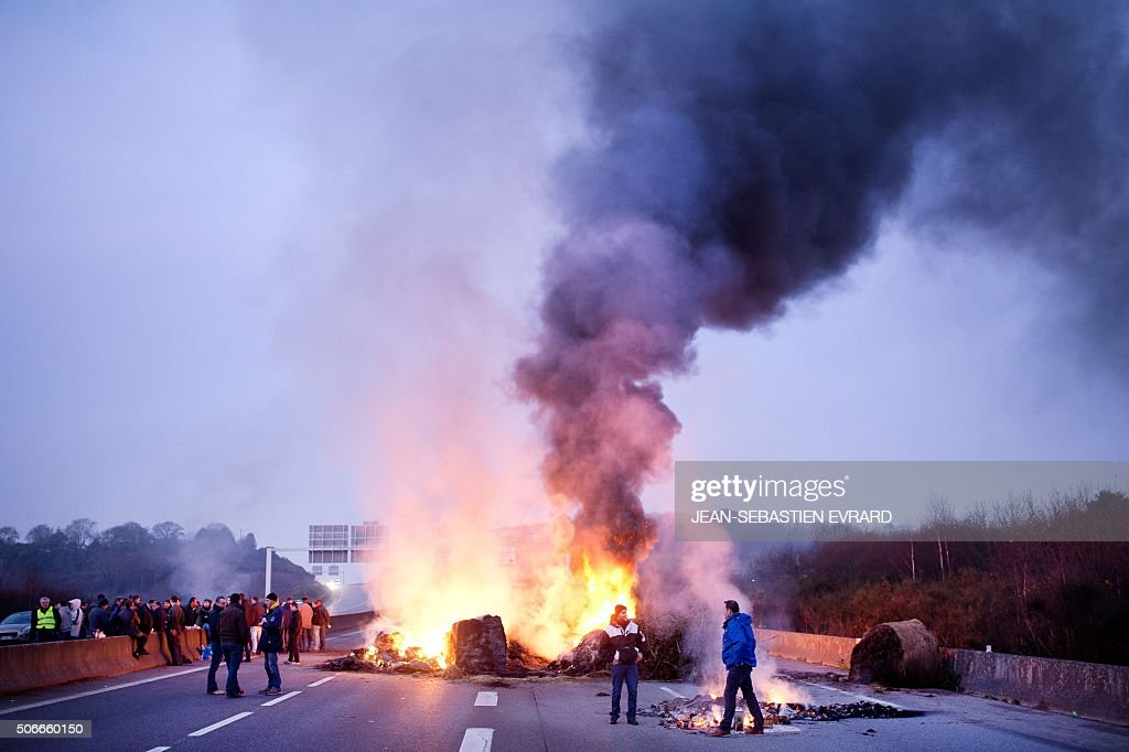 TOPSHOT - Smoke rises above a fire as French farmers block the RN 165 highway in both directions near Lorient, western France, on January 25, 2016, to protest against the falling prices of dairy and meat products. / AFP / JEAN