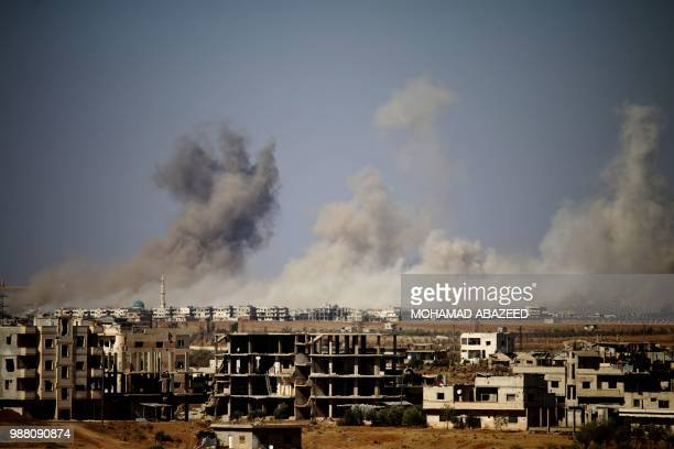 Smoke rises above a rebelheld town east of the city of Daraa during airstrikes by Syrian regime forces on June 30 2018 At least eight battered...
