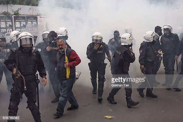 Smoke rises above as anti-riot police attempt to disperse protesters at a May Day rally in Istanbul's Bakirkoy district on May 1, 2016 in Istanbul,...