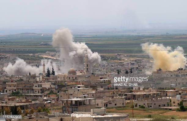 Smoke rises above buildings during shelling by Syrian regime forces and their allies on the town of Khan Sheikhun in the southern countryside of the...