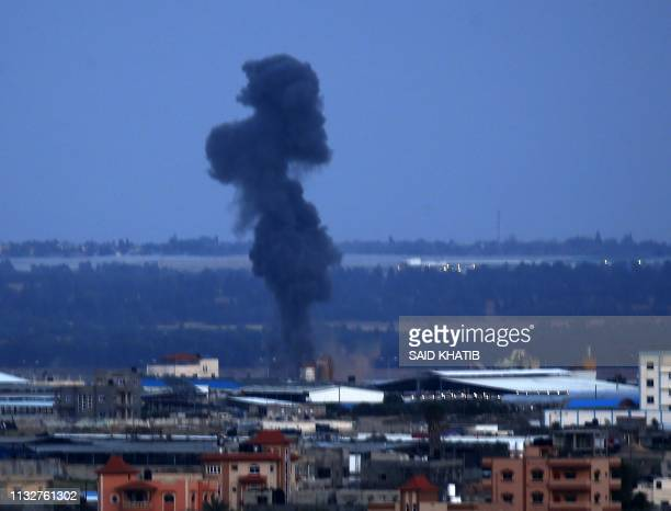 Smoke rises above buildings in Rafah, in the southern Gaza Strip during reported Israeli strikes on March 25, 2019. - Israel's military launched...