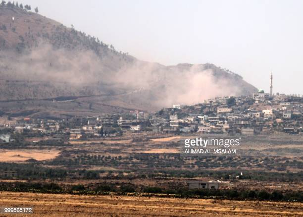 Smoke rises above buildings in the southern Syrian city of alHarah southeast of the Quneitra province during shelling by government forces on July 15...
