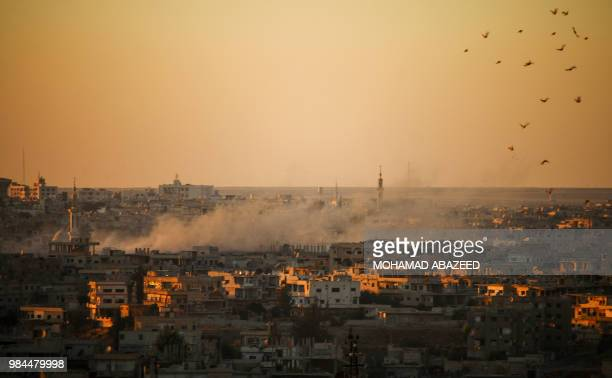 TOPSHOT Smoke rises above opposition held areas of Daraa during airstrikes by Syrian regime forces on June 26 2018 Russianbacked regime forces have...