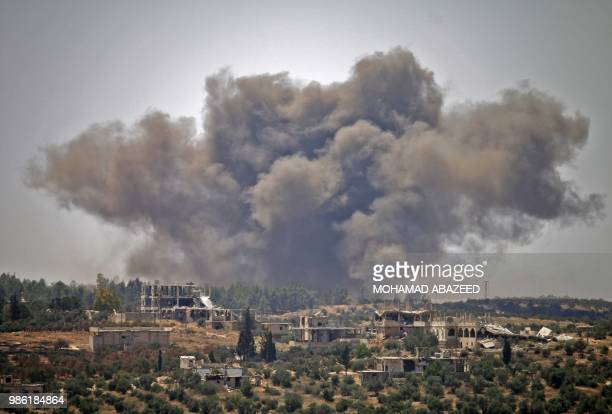 TOPSHOT Smoke rises above opposition held areas of the city of Daraa during airstrikes by Syrian regime forces on June 28 2018 Syrian government...
