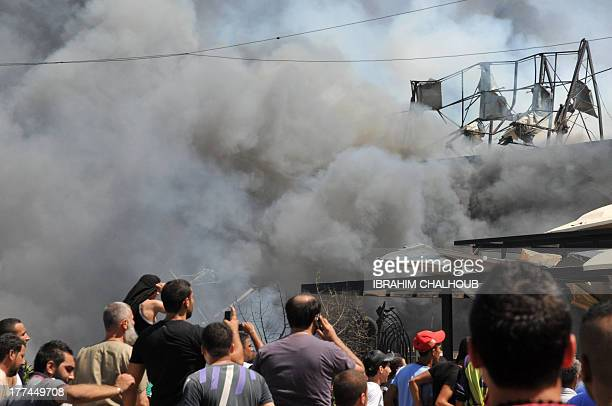 Smoke rises above people gathering near altaqwa mosque on the site of a powerful explosion in the northern Lebanese city of Tripoli on August 23 2013...