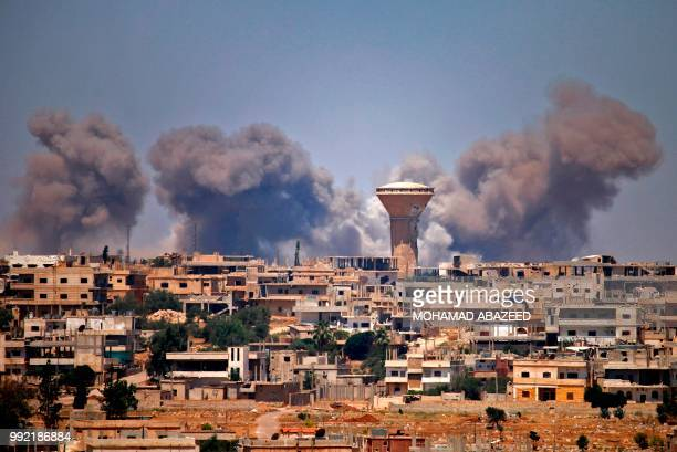 TOPSHOT Smoke rises above rebelheld areas of the city of Daraa during reported airstrikes by Syrian regime forces on July 5 2018 Waves of air strikes...