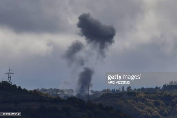 Smoke rises after a shelling next to the Ghazanchetsots Cathedral in the historic city of Shusha, some 15 kilometers from the disputed...
