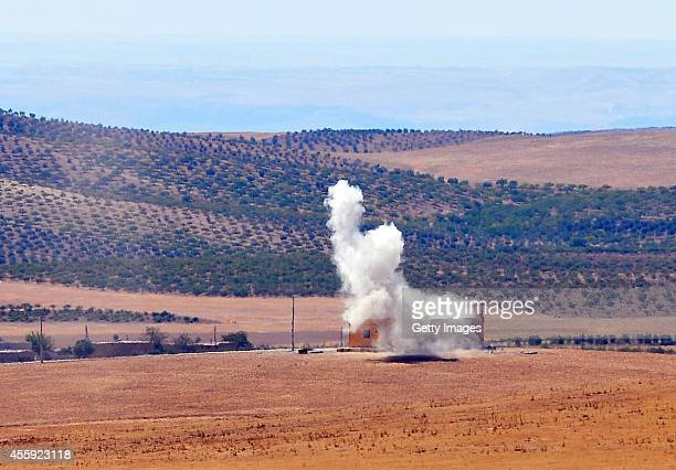 Smoke rises after Protection of the Kurdish People fighters hit a target as they clash with possible Islamic State soliders near the Syrian side of...