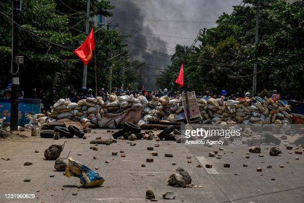 Smoke rises after protesters burn tyres as they gather to continue their protest against military coup and detention of elected government members in...