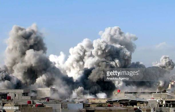 Smoke rises after Syrian regime forces dropped barrel bomb on Al Sahara village of Aleppo Syria on January 30 2014 At least 32 people were killed...